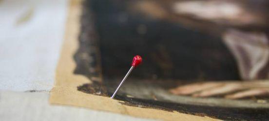 Préparation du pliage des angles avant remontage d'une toile sur châssis